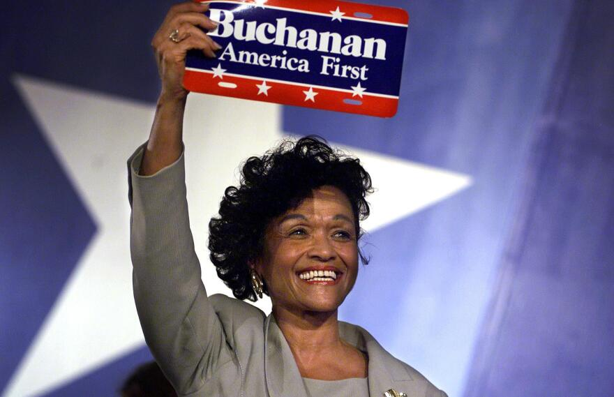 """Reform Party vice presidential candidate Ezola Foster holds up an """"America First"""" sign after her nomination acceptance speech in August 2000. Foster, the first African American woman to be nominated for the position, was running on the Reform ticket with presidential candidate Pat Buchanan."""