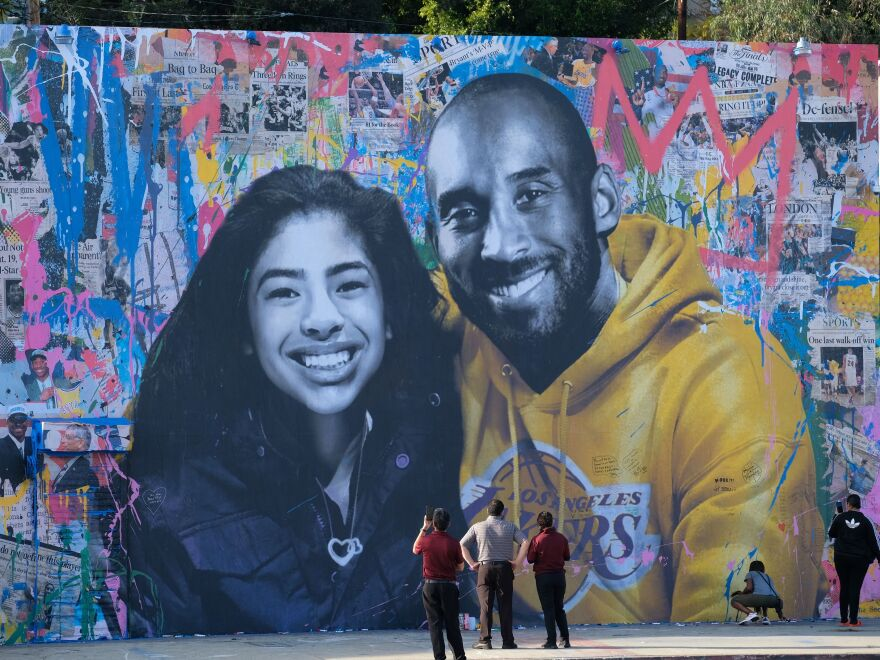 People stop to take pictures in front of a mural depicting Kobe Bryant and his daughter Gianna. They and seven other people were killed in a helicopter crash last month in Calabasas, Calif.