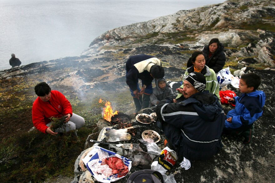 Arne Lange, a 39-year-old Inuit fisherman, and his family barbecue seal meat on an island near the village of Ilimanaq, Greenland in 2007.