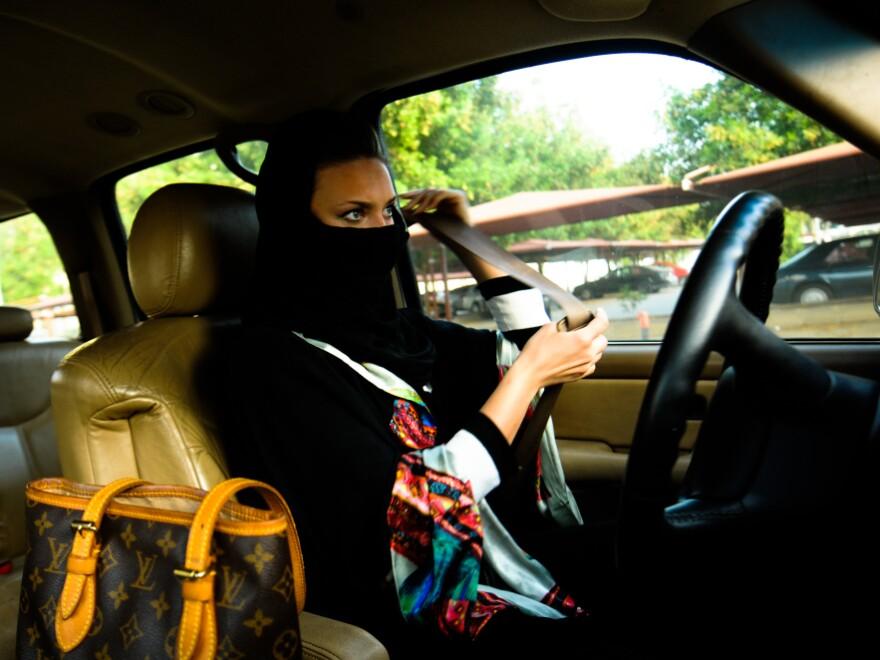 A Saudi woman fastens her seat belt before driving in Jeddah, western Saudi Arabia.