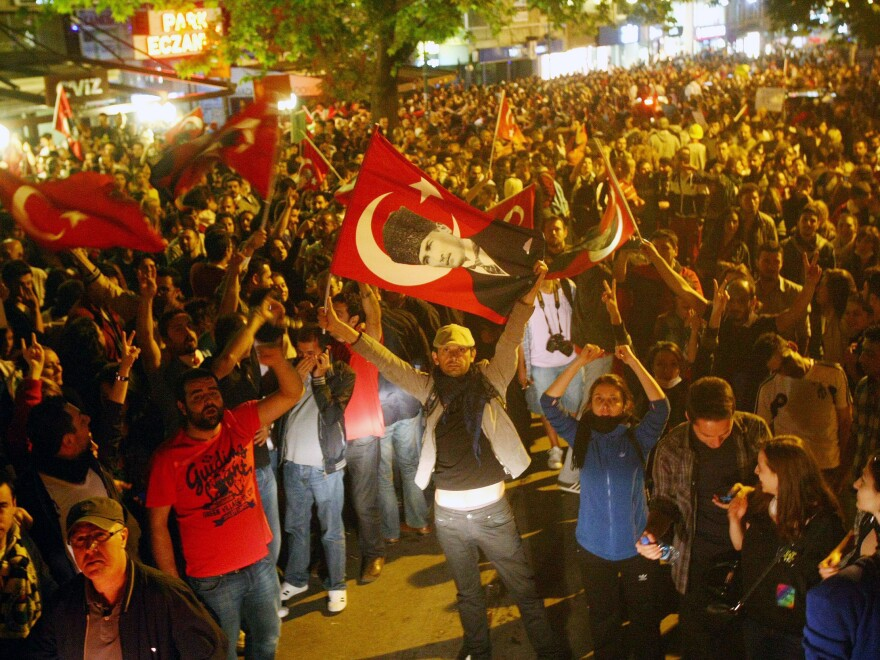Anti-government protesters shout slogans and wave Turkish national flags during a demonstration in central Ankara on Thursday.