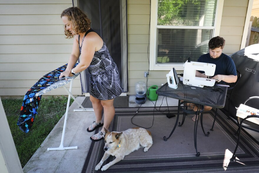 Joni Watkins and Matt Umberger sew masks to donate to health care workers, on the porch of their South Austin home.