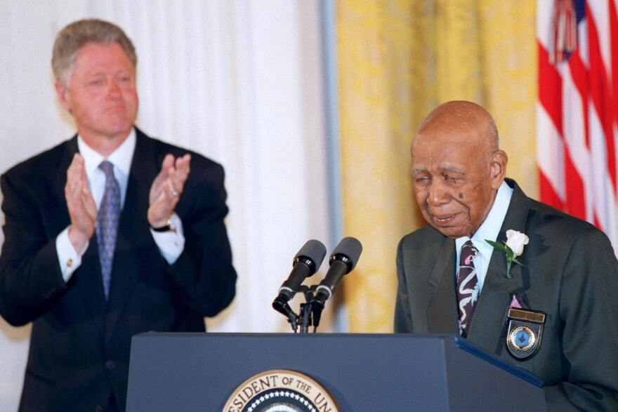 Herman Shaw speaks as President Bill Clinton looks on during a White House event where Clinton apologized to the survivors and families of the victims of the Tuskegee Syphilis Study. Shaw was one of hundreds of Black men who were part of a government study that followed the progress of syphilis and were told that they were being treated, but were actually given only a placebo.