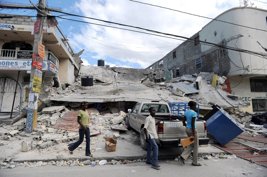 Pedestrians walk past the rubble of a building destroyed by a massive earthquake in Port-au-Prince, Haiti, on Jan. 13, 2010. Tens of thousands perished in the quake.