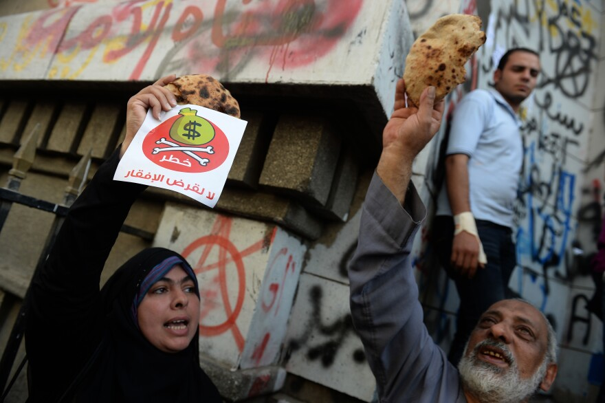 """Egyptian protesters hold bread along with fliers reading """"Danger, no to loans that lead to poverty"""" during a rally Wednesday in Cairo. An International Monetary Fund delegation is in Cairo for talks on a loan needed to lift Egypt's economy out of crisis."""