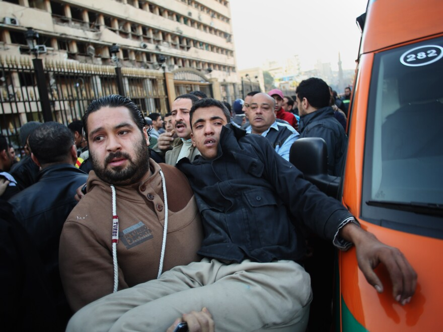 A man carries an Egyptian police officer to an ambulance after Friday's blast at the Egyptian police headquarters in downtown Cairo.