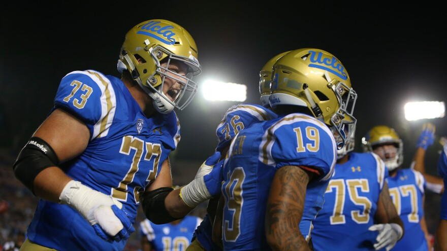 UCLA players celebrate during a game against the Arizona Wildcats at the Rose Bowl last year in Pasadena, Calif. Gov. Gavin Newsom has signed a bill paving the way for college athletes in the state to hire agents and sign endorsement deals.