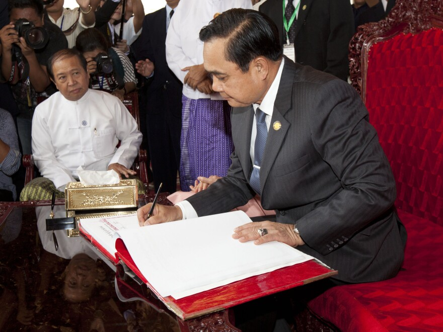 Thailand's Prime Minister Prayuth Chan-ocha signs a guest book Friday during his visit to Shwedagon Pagoda, a landmark in Myanmar, also known as Burma.