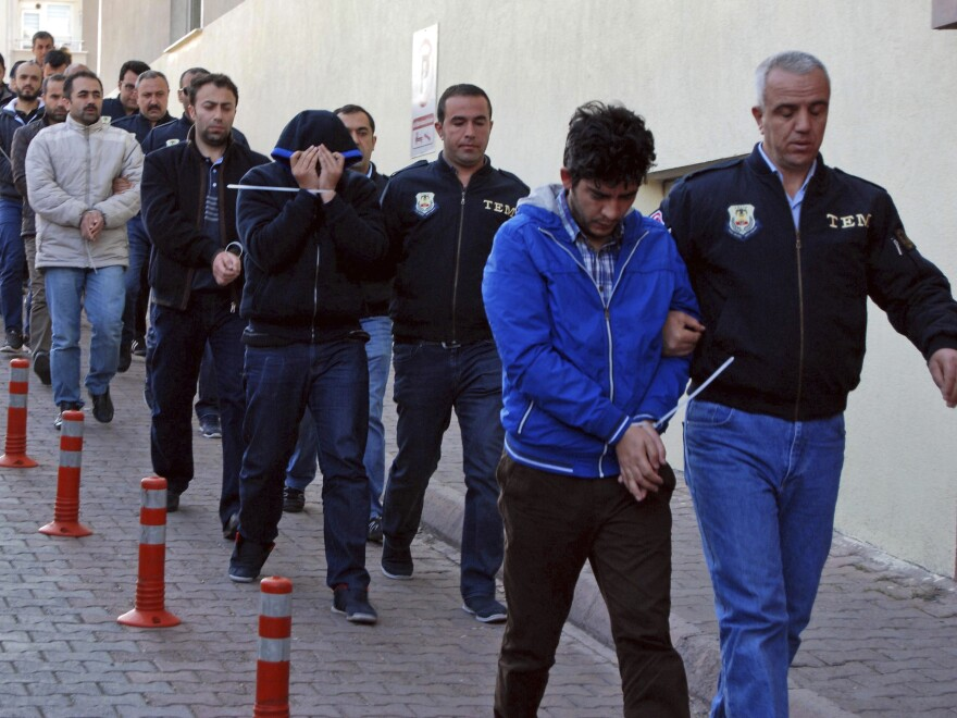 Police officers escort detainees in Kayseri, Turkey, on Wednesday. Turkish authorities say the countrywide raids were aimed at people with suspected links to U.S.-based cleric Fethullah Gulen.