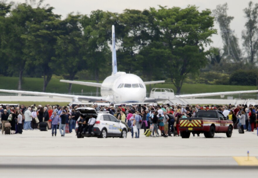 People stand on the tarmac at the Fort Lauderdale-Hollywood International Airport in Florida on Friday after a shooter opened fire inside a terminal, killing at least five people and wounding eight others before being taken into custody.