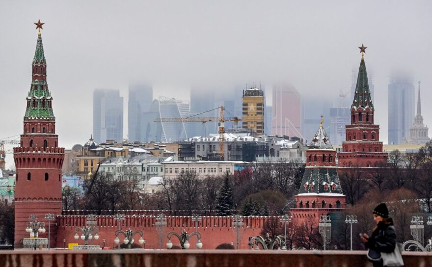 A woman walks in front of the Kremlin and skyscrapers in Moscow. The fallout from an  alleged Russian hacking effort to target federal agencies continues as Russian President Vladimir Putin congratulated President-elect Joe Biden on his victory.