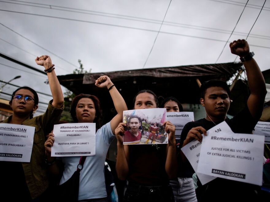 Supporters of Kian delos Santos protest on Thursday outside the police station where three policemen involved in Kian's killing were assigned in Manila.