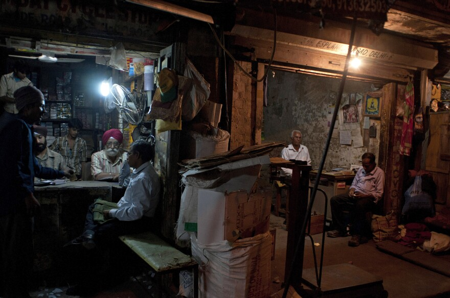 Indian workers at a spare parts store discuss business as the proprietor of a neighboring business sits in his shop in New Delhi.