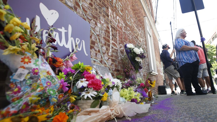 A memorial to Heather Heyer — who was killed at last year's Charlottesville rally by a driver facing murder and hate crime charges — lies at the site of her death. Heyer's mother, Susan Bro, is in the background.