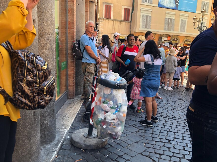 Tourists stand near an overflowing garbage receptacle near the Trevi Fountain.