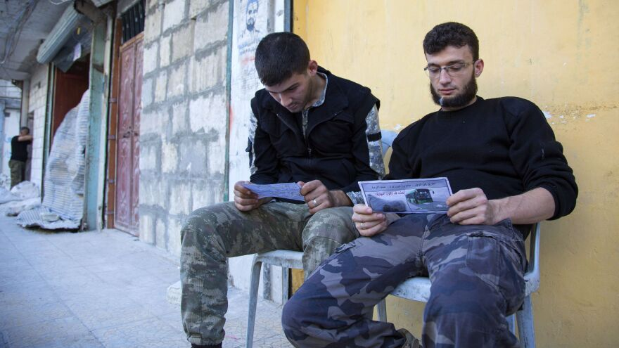"Opposition fighters in Aleppo look at fliers reportedly distributed by the Syrian government. The fliers encourage rebels to leave the eastern parts of the city. The Syrian army and its Russian ally have declared a ""humanitarian pause,"" but there were few signs rebels or civilians were leaving."