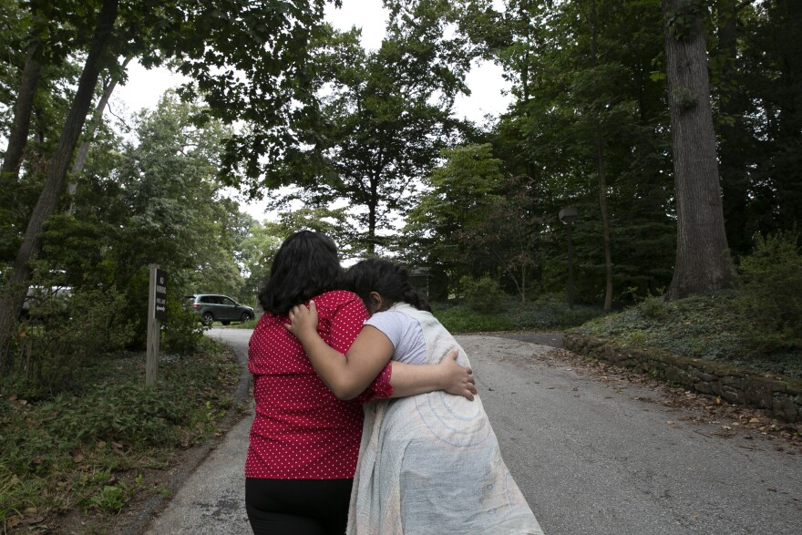 Maria gives Rosa a hug while they go for a walk.
