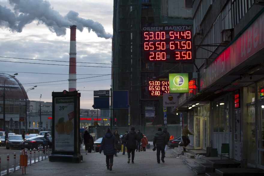 People walk past a display with currency exchange rates in Moscow on Wednesday. Falling oil prices have contributed to a number of economic problems, including a currency that has fallen from 35 rubles to the dollar this summer to more than 50 rubles to the dollar now.
