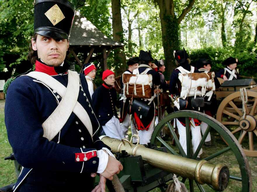 Belgium's plan to honor the Battle of Waterloo displeased France. In this photo, an enthusiast dressed as a member of the French army stands next to a cannon before the re-enactment of the famous battle.