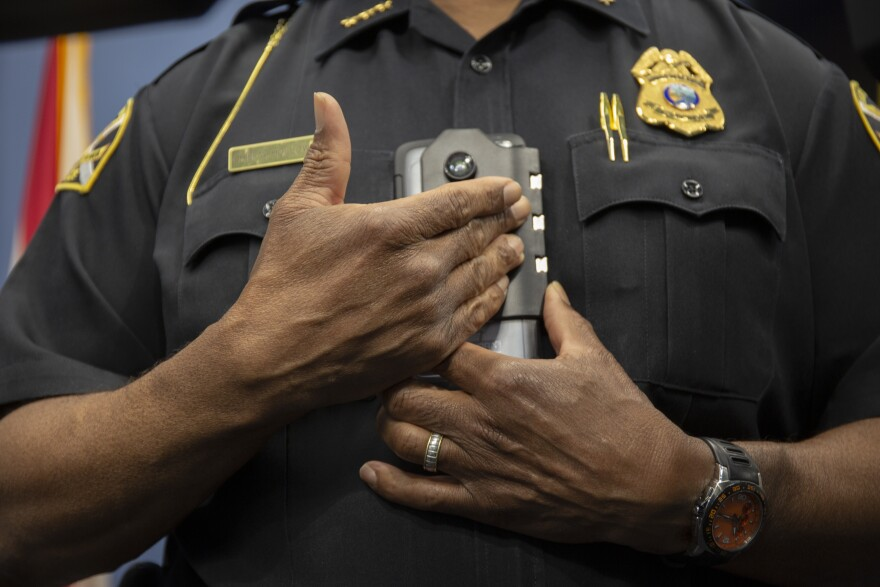 A uniformed police officer holds up a plastic clip that secures a smartphone style device used as a body cam.