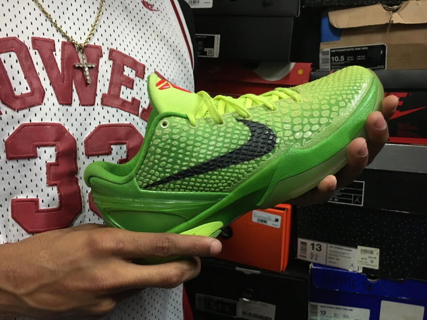 Davon Artis holds a pair of Kobe 6 Grinch shoes, released in 2010. The shoes more than doubled in value within hours of Bryant's death.