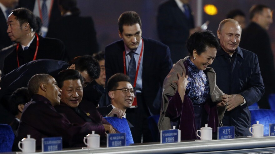 Russia's President Vladimir Putin (right) helps put a shawl or coat on Peng Liyuan, wife of China's President Xi Jinping, as Xi talks to President Obama during a fireworks show celebrating the Asia-Pacific Economic Cooperation session in Beijing.