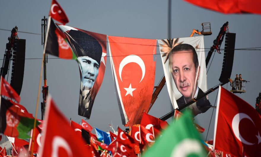 Turkish special force police officers stand guard next to a banner picturing the late Mustafa Kemal Ataturk (left) and Turkish President Recep Tayyip Erdogan as people wave Turkish national flags during a rally this week in Istanbul against the failed July 15 coup.