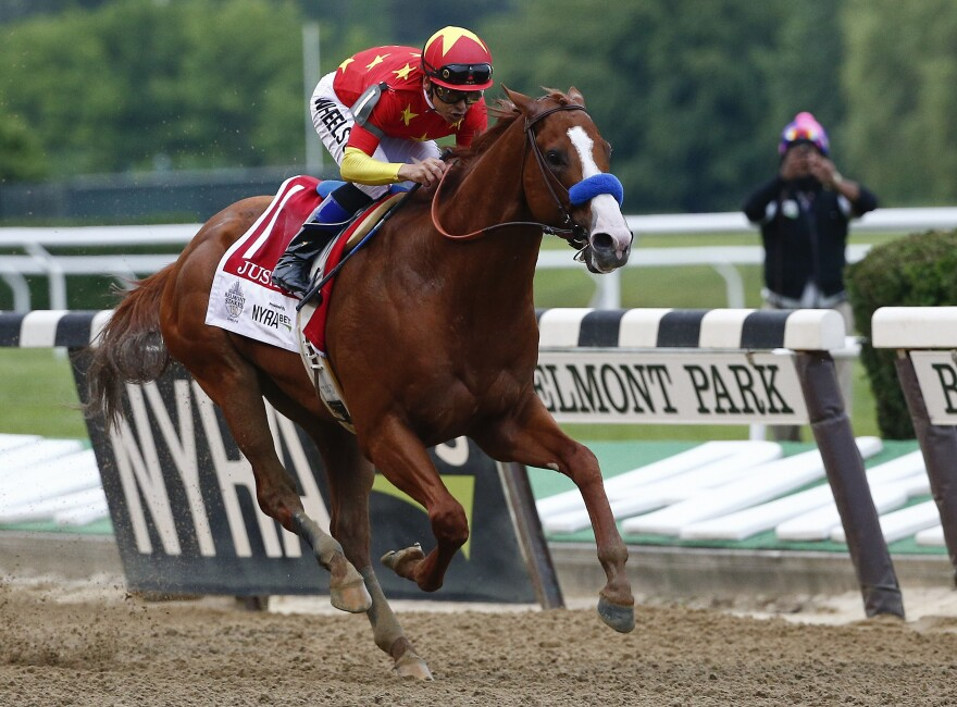 Justify, with jockey Mike Smith aboard, crosses the finish line to win the 150th running of the Belmont Stakes horse race, and the rare Triple Crown title on Saturday in Elmont, N.Y.