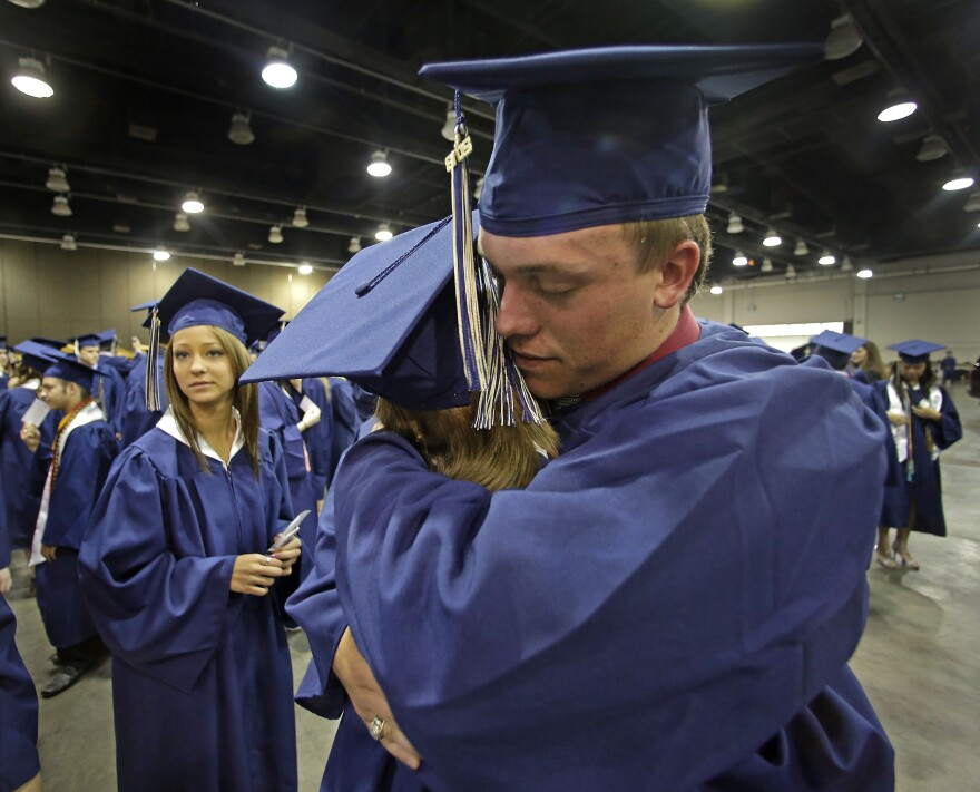 Southmoore High School senior Jake Spradling hugs a classmate as they get ready to attend their commencement ceremony in Oklahoma City on Saturday.