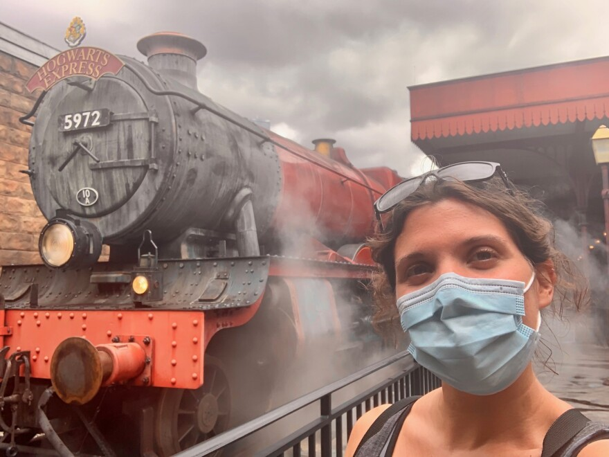 Stephanie Colombini wearing a mask in front of the Hogwarts Express train ride.