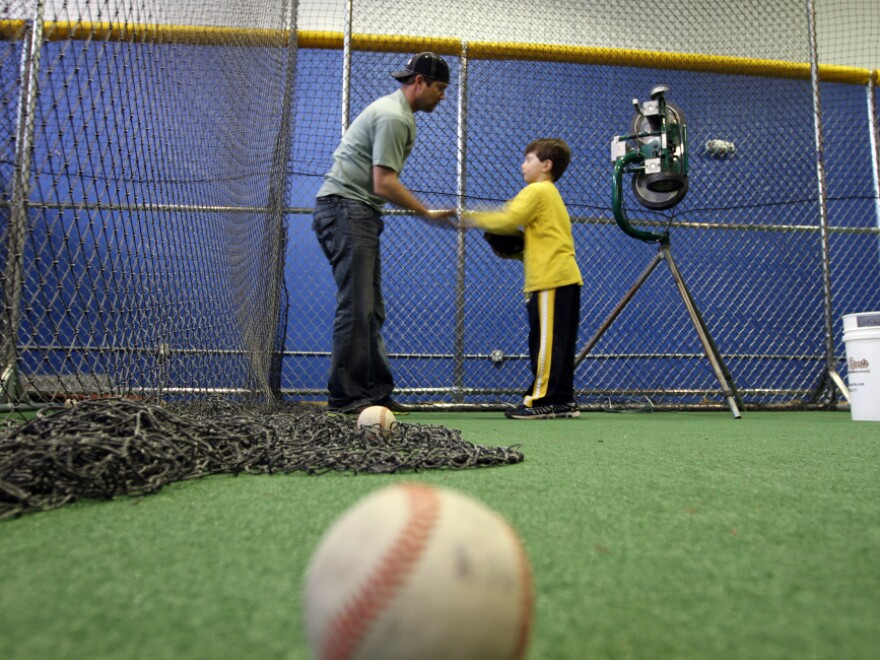 Minor league baseball player Reid Gorecki gives a young player instructions at a training center on Long Island, N.Y.