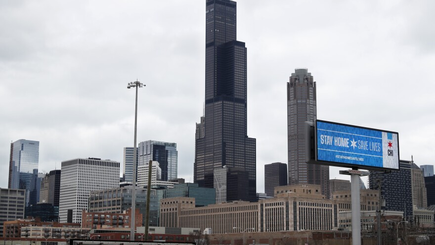 A public service message Stay Home Saves Lives is seen against the Chicago skyline Monday, March 30, 2020.