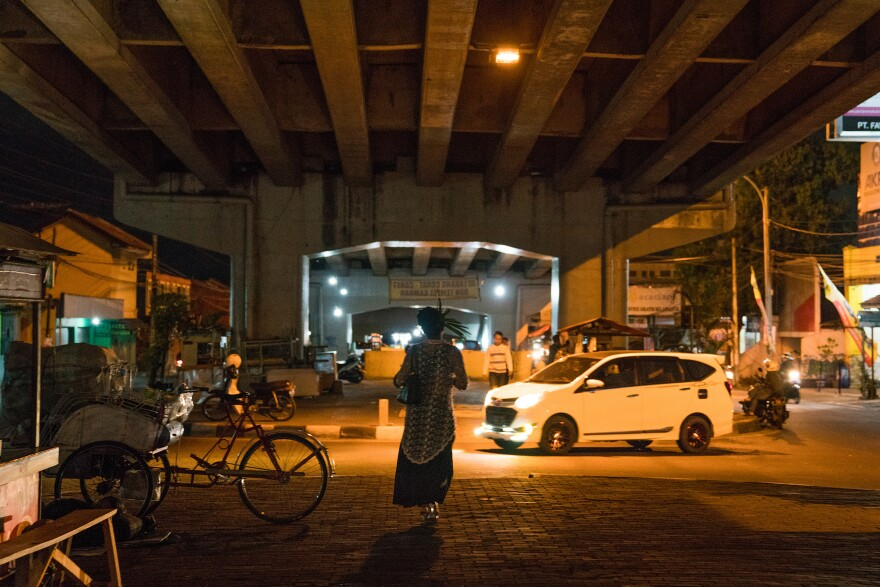 Madame Ruly walks under a busy highway underpass where she goes to sing for tips in Yogyakarta, Indonesia. Waria, loosely translated as transgender women, have been part of Indonesian society for as long as anyone can remember.