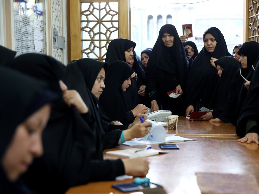 Iranian women vote in the parliamentary and Experts Assembly elections at a polling station in Qom, 78 miles south of the capital, Tehran, on Friday.