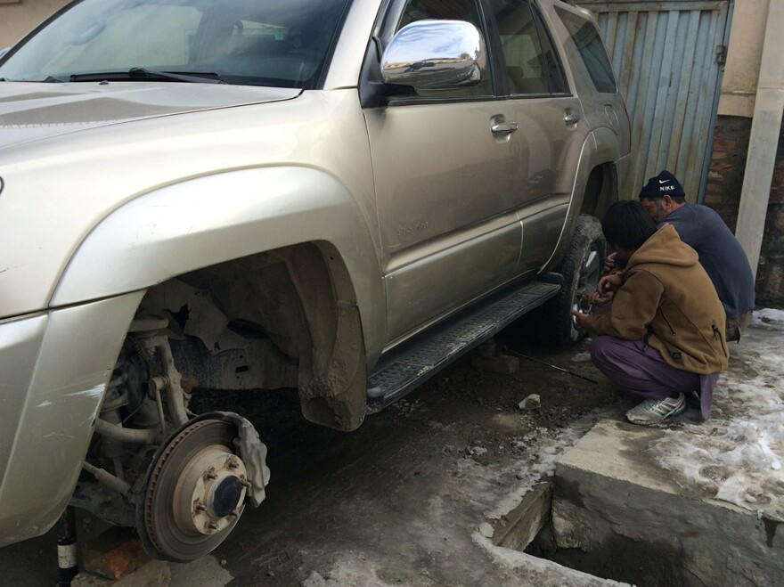 Men change the flat tires on the car of an NPR guest in Kabul.