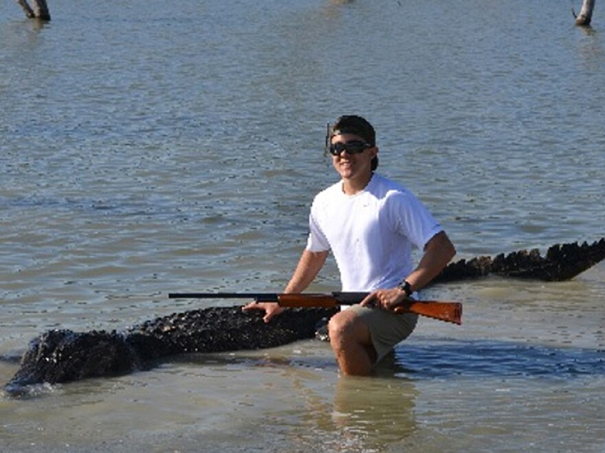 A photo provided by the Texas Parks and Wildlife Department shows Braxton Bielski with the 800-pound alligator he killed.