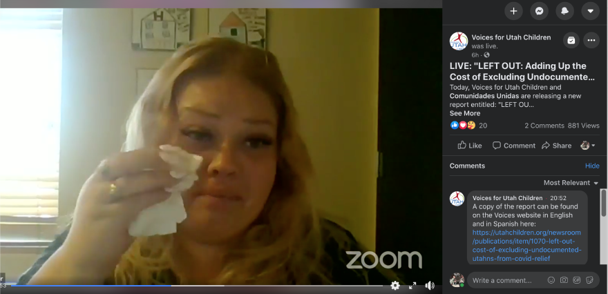 Screengrab of a woman talking on a video call and wiping her eye with a tissue