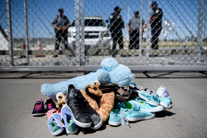 Security personnel stand before shoes and toys left at the Tornillo Port of Entry, where minors crossing the border illegally have been housed after being separated from adults, back on June 21.