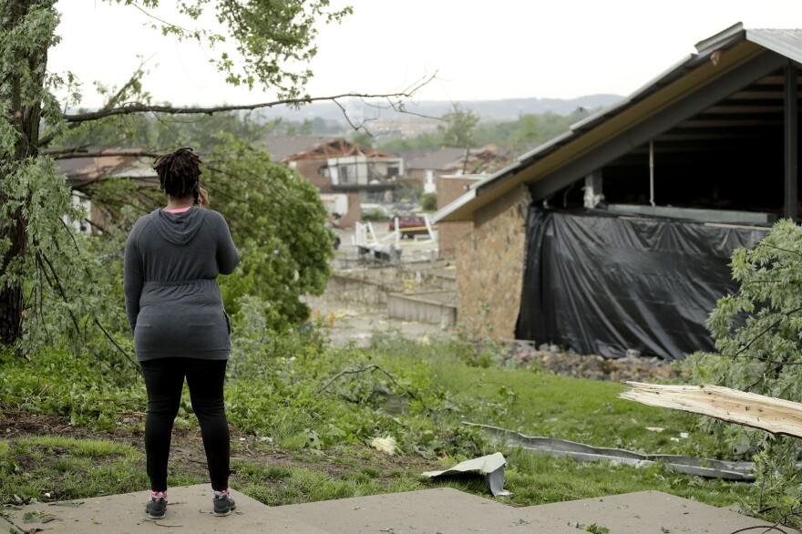 A woman surveys tornado damage on Thursday.