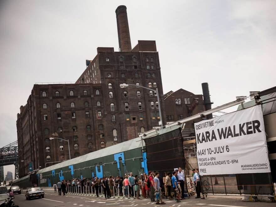 "Visitors wait in line for the Kara Walker exhibit on May 10, opening day. The show was housed in a former Domino Sugar refinery. Inside, visitors described the building as ""cathedral-like"" and ""creepy"" and said it smelled like a bakery."