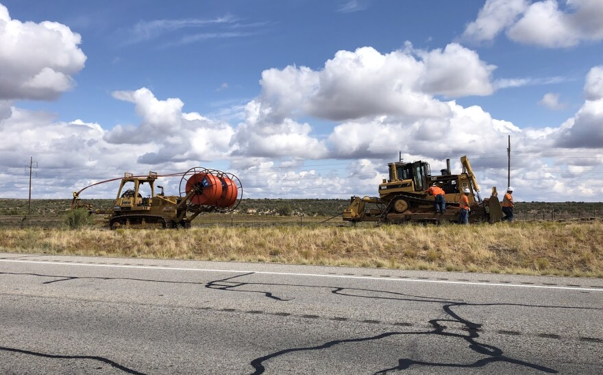 A heavy machine holding a spool of orange cable drives along the highway behind a tractor.
