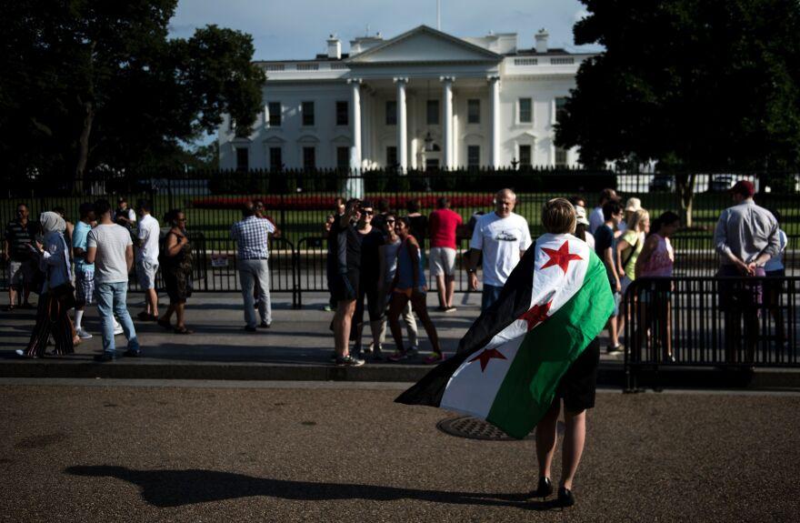 A woman walks with a Syrian flag during a rally for World Refugee Day across from the White House in Washington, D.C., on June 20.