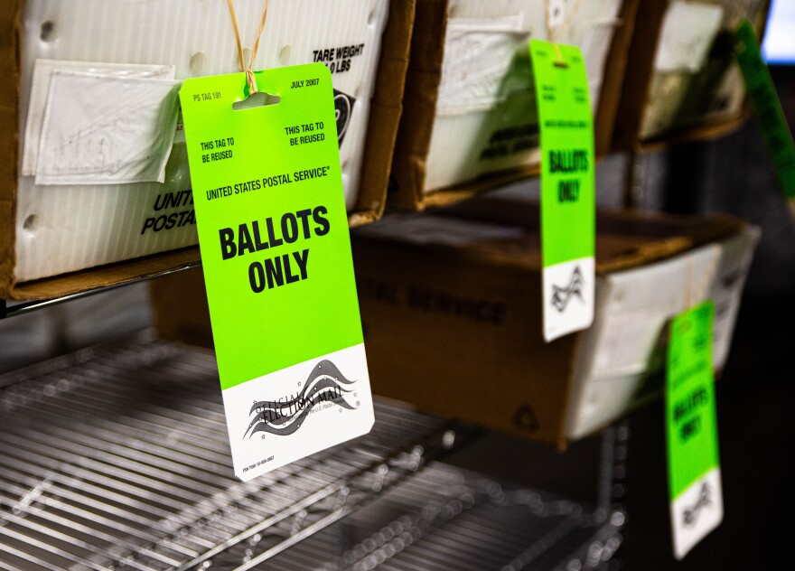 "A box of absentee ballots that read ""Ballots Only"" in bold yellow, sits on shelves waiting to go out for delivery."