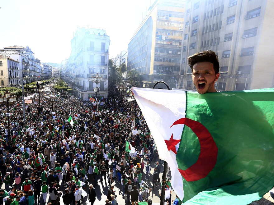 Algerian shouts as he holds the national flag during a protest in Algiers, Algeria, on Friday.