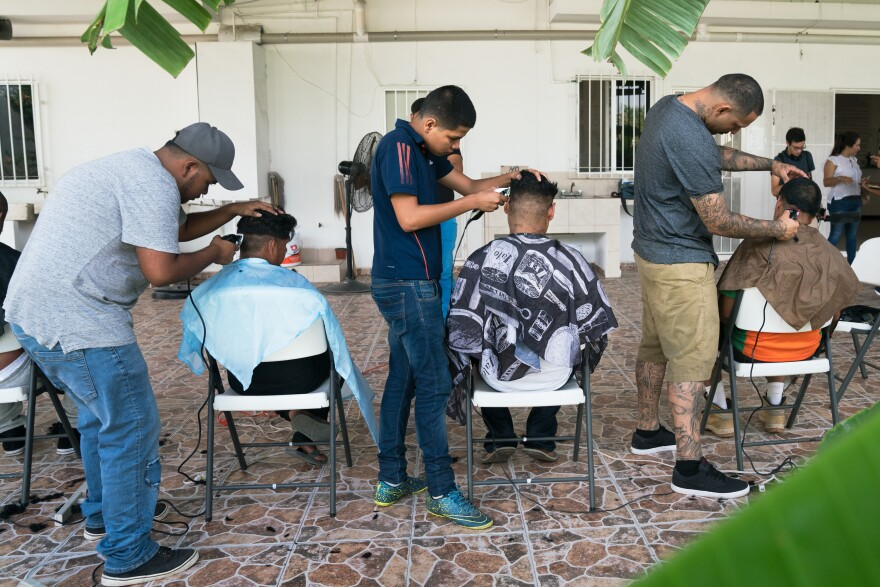 Volunteer barbers provide haircuts for migrants staying at the shelter.