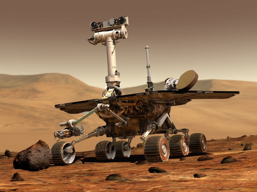 An artist's concept portrays a NASA rover exploring the surface of Mars.