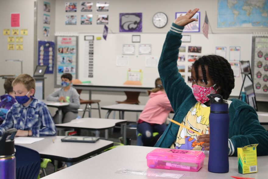A student raises her hand in a modern classroom at Rhein Benninghoven Elementary, which was built in 2017. Shawnee Mission wants to rebuild some of its oldest elementary schools with rising maintenance costs.