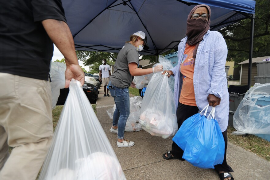 Emily Dragoo, center, a teacher at Apollo Jr. High, hands out food to Richardson Independent School District families at a distribution site in Dallas in May.