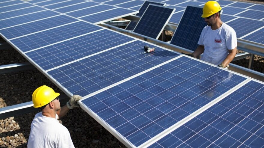Contractors with SunEdison install more than 1,000 Chinese-made solar panels on top of a Kohl's Department Store in Hamilton Township, N.J., in 2010. Energy generated by the solar system will cut the store's usage, on average, by 25 to 30 percent.
