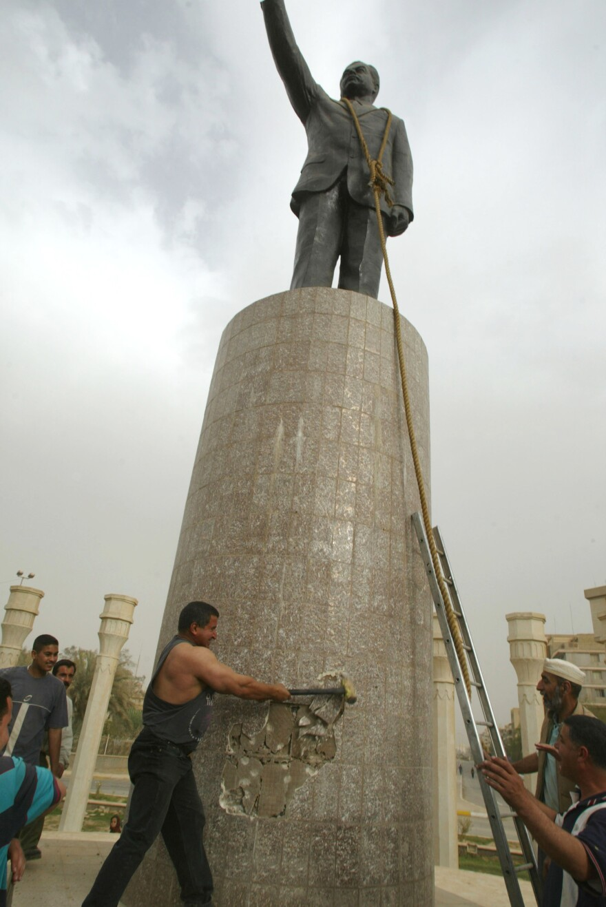 """""""Now, I really regret hitting the statue,"""" says Qatham Sherif al-Jabouri, shown here on April 9, 2003, helping to topple a Saddam Hussein statue in Baghdad."""